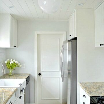 view of white galley style kitchen reveal and DIY refrigerator cabinet