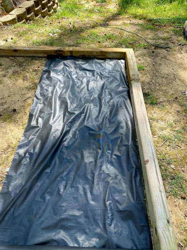 laying weed control fabric in raised planter bed