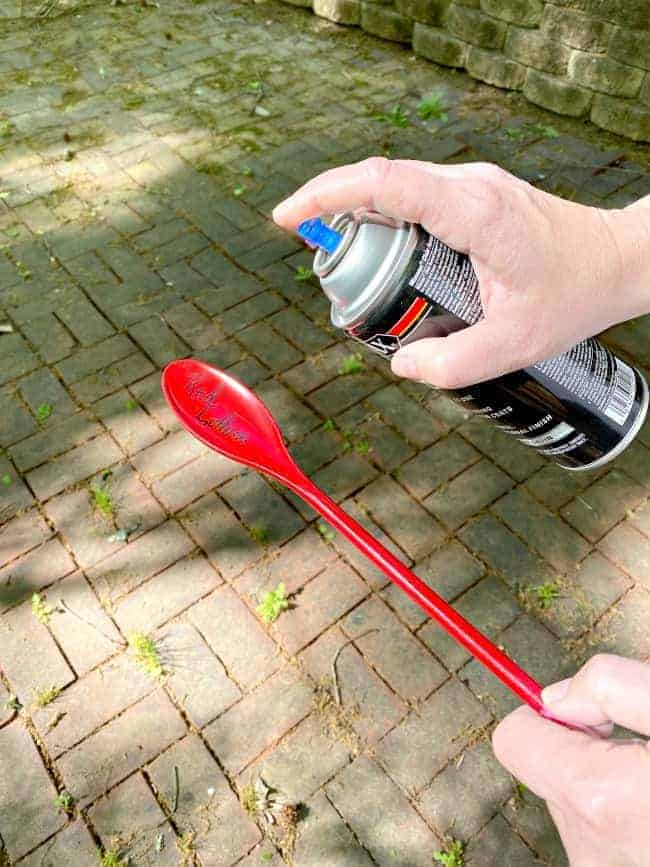 spraying poly on red plastic veggie garden marker