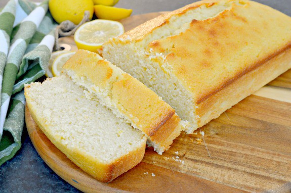 sliced lemon loaf on cutting board with lemons in background