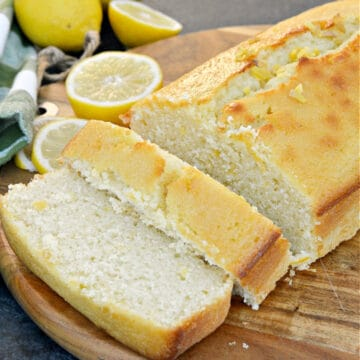 sliced lemon loaf on cutting board with lemons in background