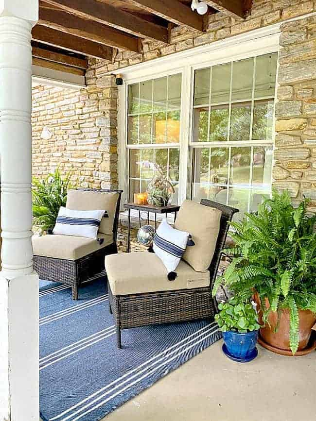 covered front porch decorated for summer with pillows on 2 chairs and a blue striped area rug