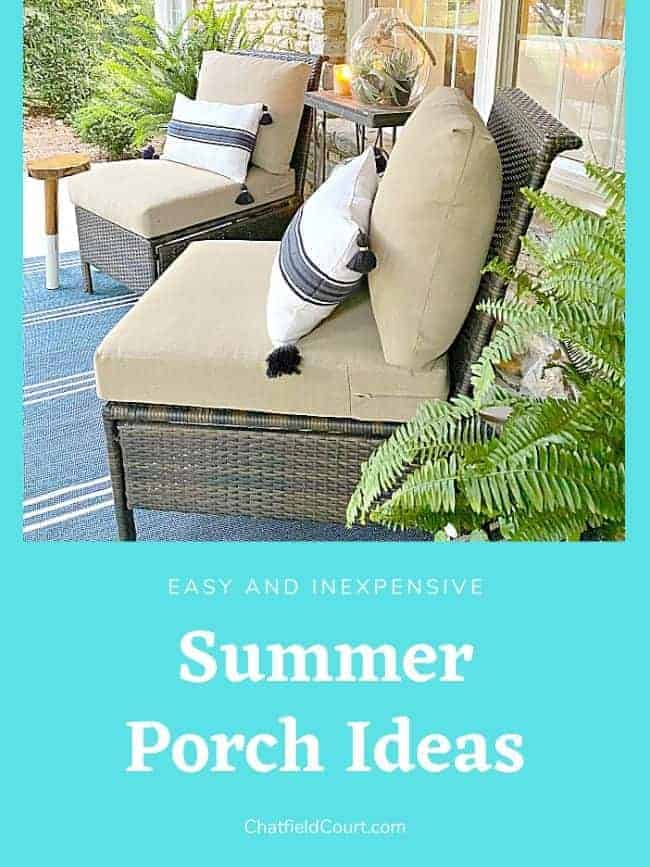 covered front porch decorated for summer with 2 chairs with pillows and potted plants