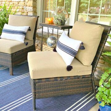 front porch of stone cottage with 2 wicker chairs with pillows on them and a striped blue rug on the ground
