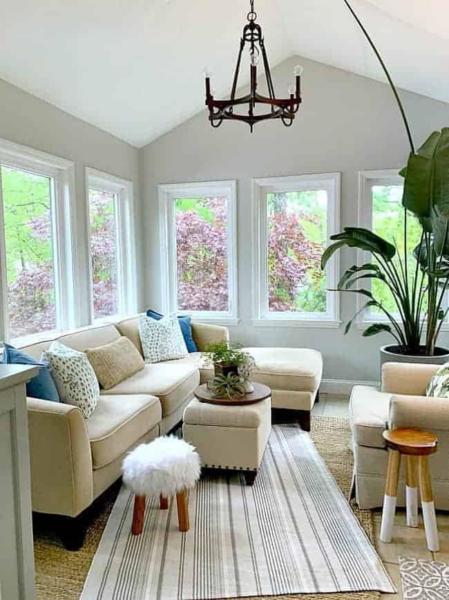sunroom with sectional sofa, large hanging light and large plant in corner
