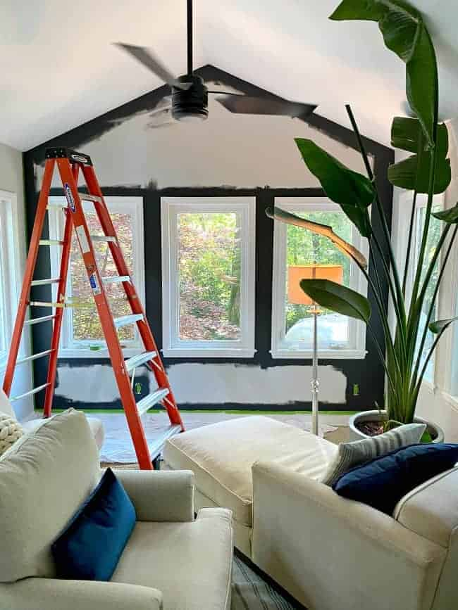 painting an accent wall dark gray in a sunroom with 3 windows looking outside