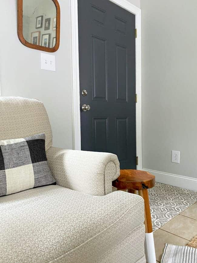 linen colored arm chair with dark gray painted door in the background
