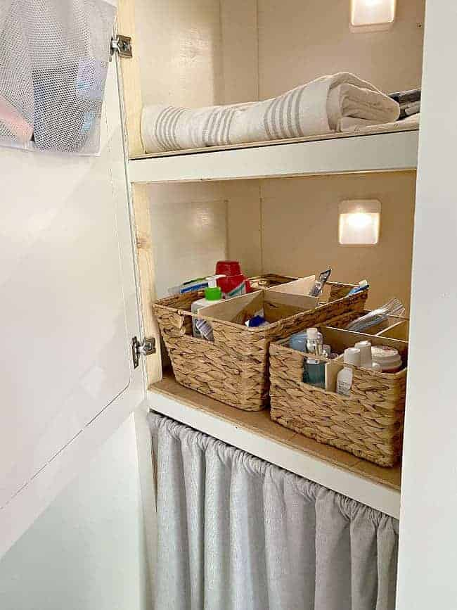 woven basket with DIY dividers in linen closet filled with toiletries