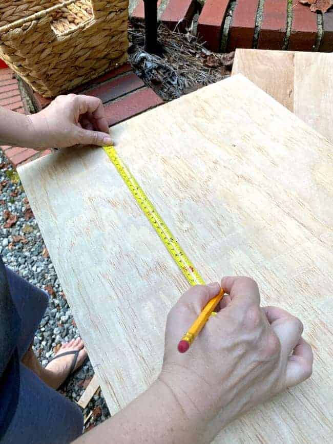 marking measurements on underlayment with tape measure and pencil