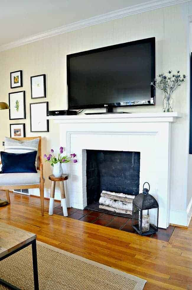 white painted fireplace with birch logs inside and a large tv on the mantle