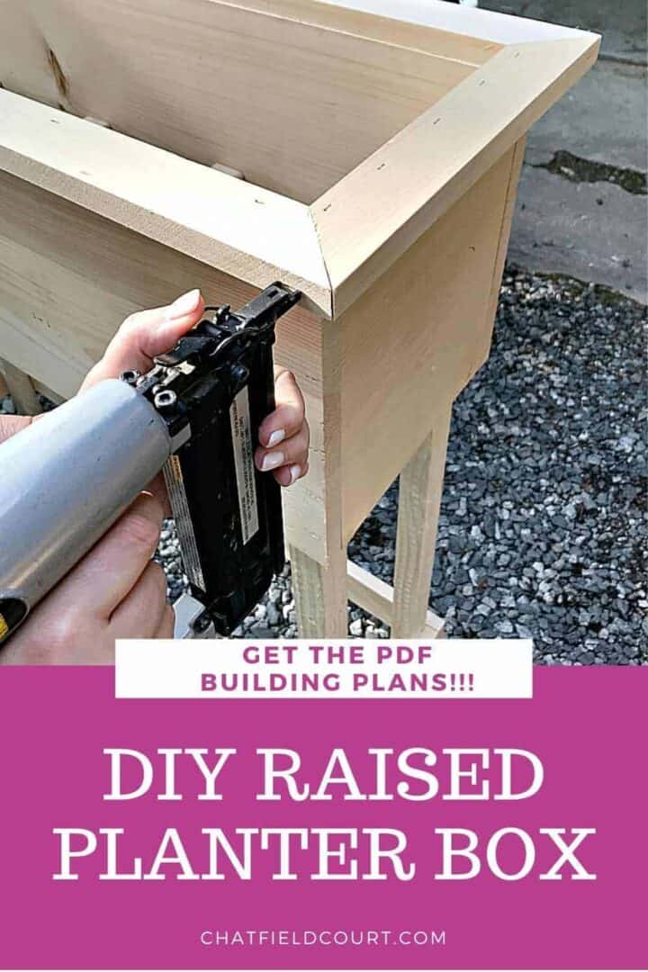 nailing wood on raised planter box and large graphic