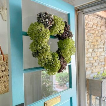 dried hydrangea wreath hanging on a turquoise door