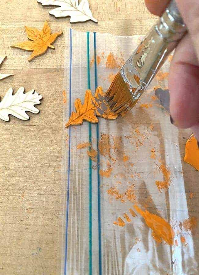 painting wooden craft leaves with orange paint