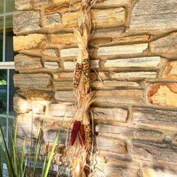 mini Indian corn and raffia hanger on stone wall