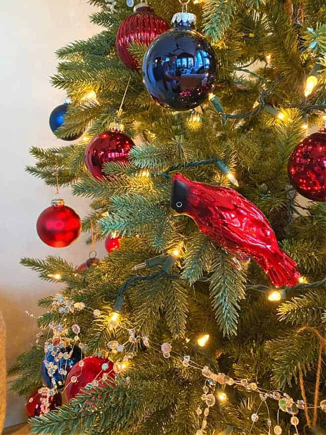 red and navy ornaments and a red cardinal ornament on a Christmas tree