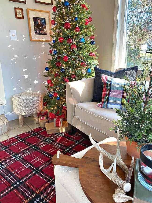 Christmas tree in corner of room with red and navy ornaments