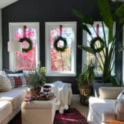 small sunroom decorated for Christmas with a red plaid rug and window wreaths