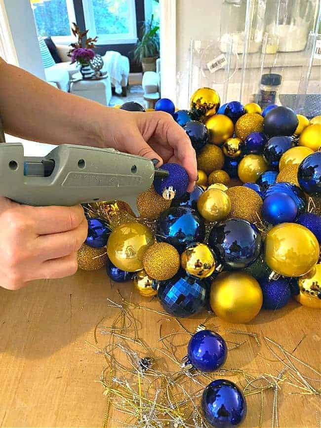 using hot glue gun to glue ornaments onto wreath