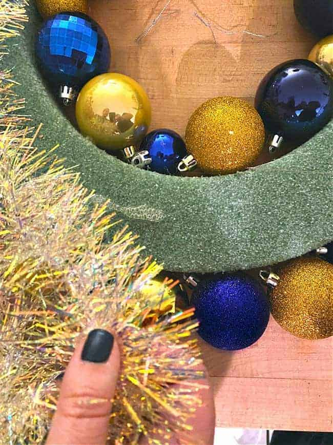gluing tinsel to wreath form with hot glue