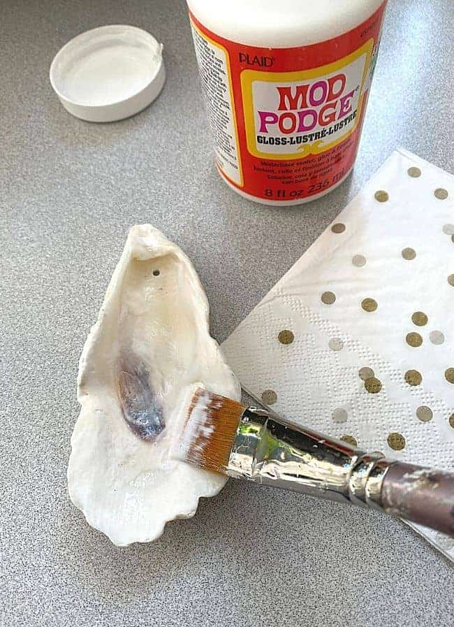 brushing Mod Podge on seashell