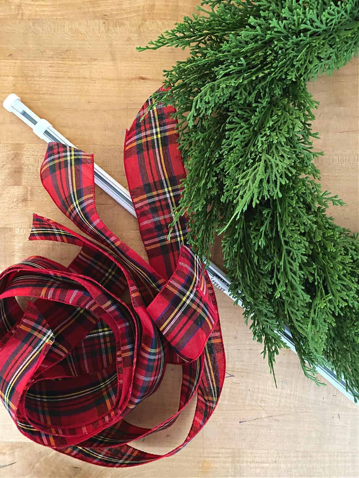 wreath, ribbon and tension rod on a butcher block