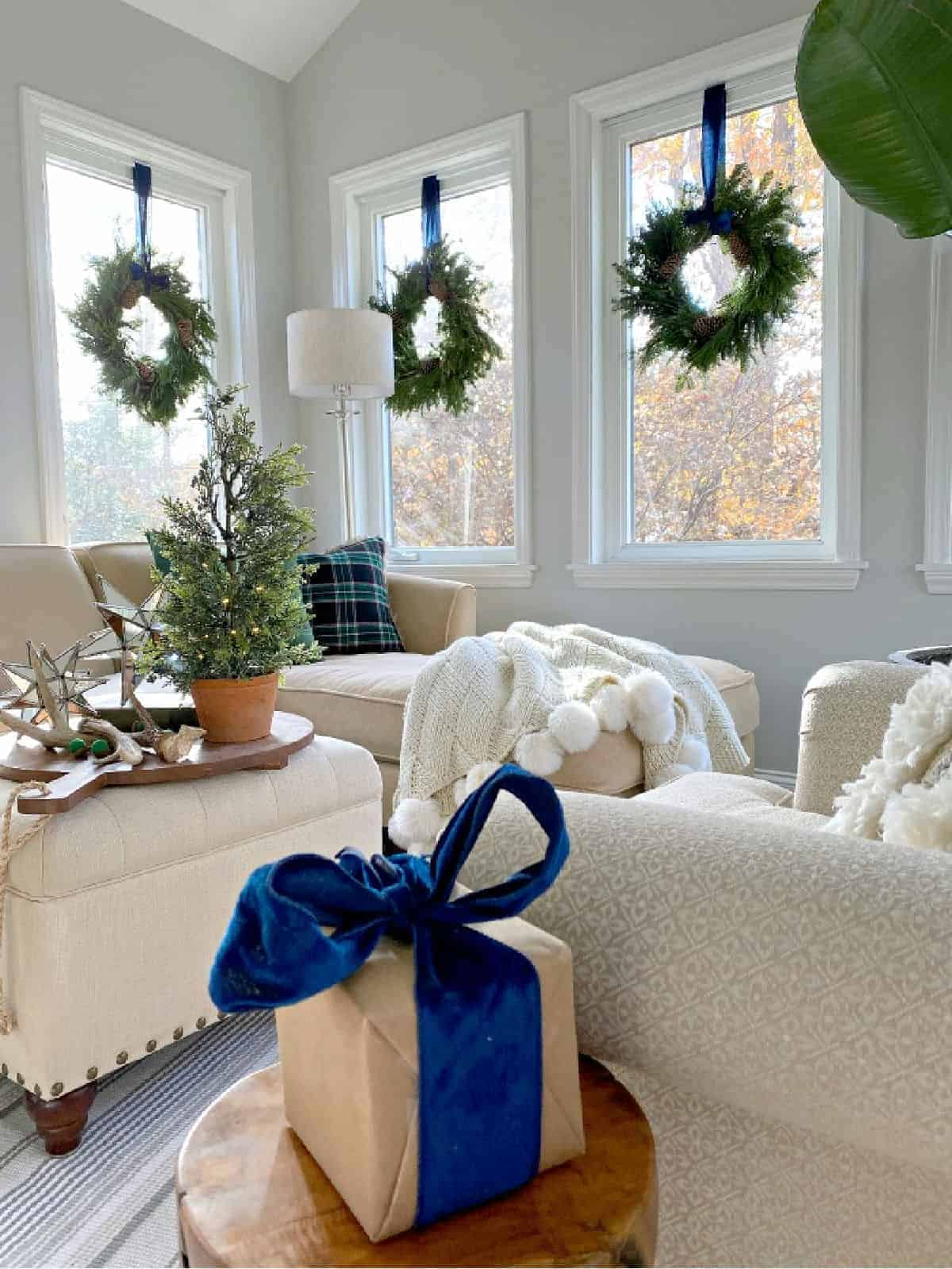 Christmas wreaths hanging in windows with blue velvet ribbon