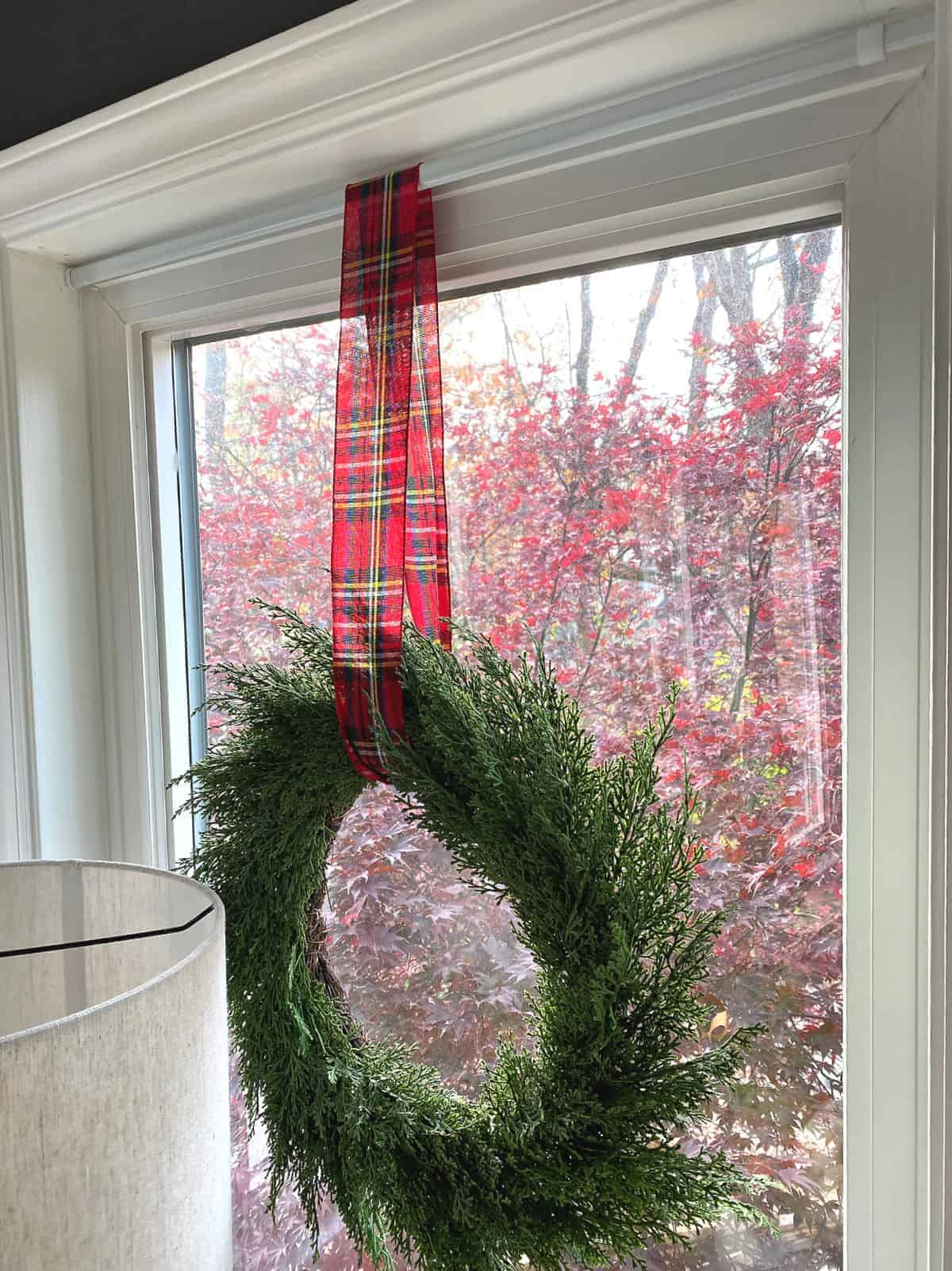 wreath hanging in window with red checked ribbon