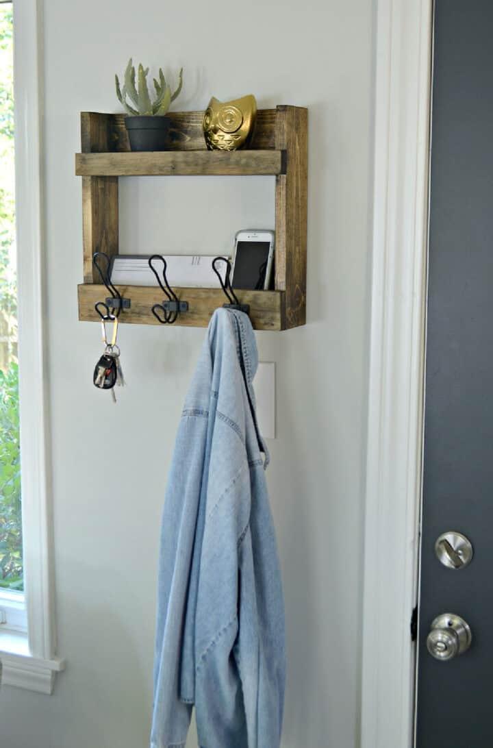 DIY coat rack with shelves hanging on wall next to door