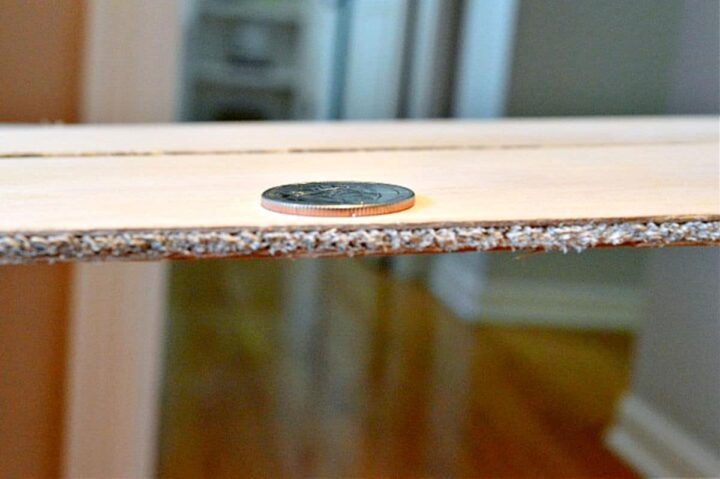 quarter on top of piece of plywood to show thickness