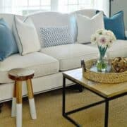 new white sofa in living room with blue and white pillows