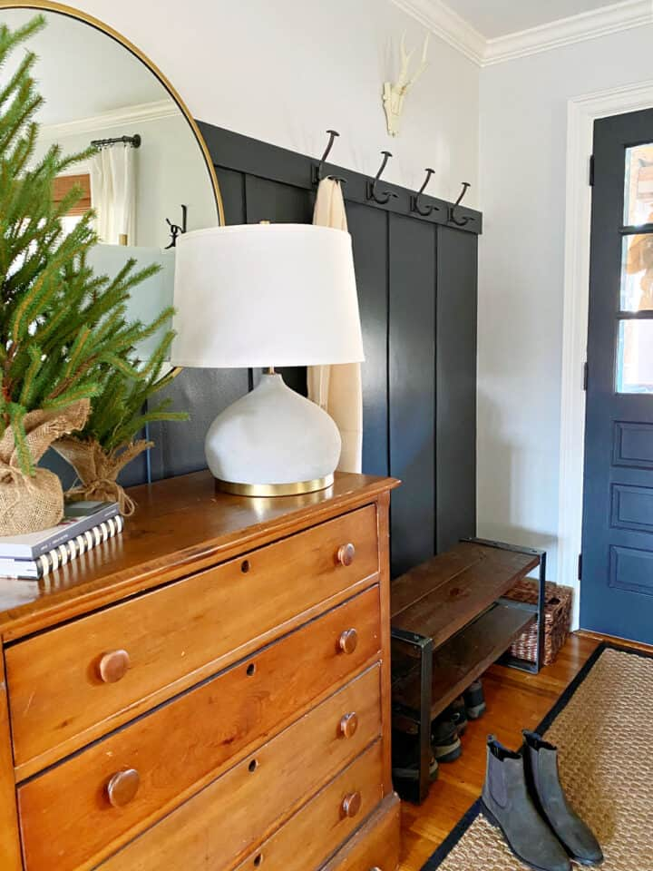 small entry with dark painted front door and board and batten accent wall