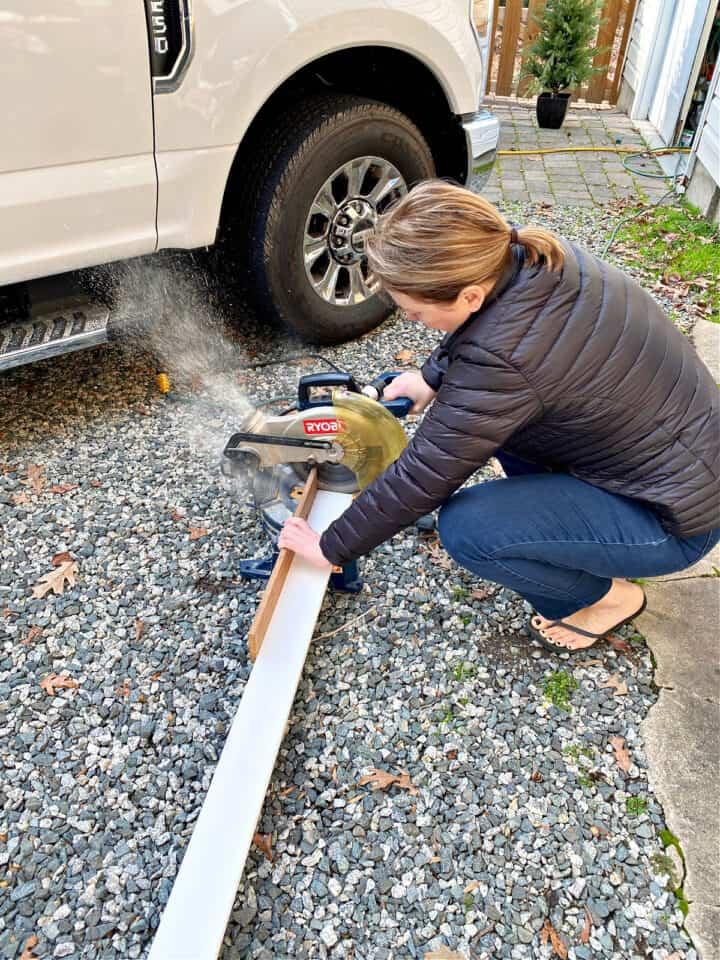 woman cutting wood on miter saw