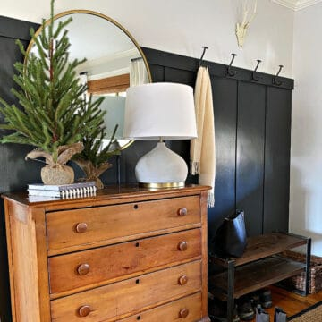 a dark wall in an entryway with a cabinet
