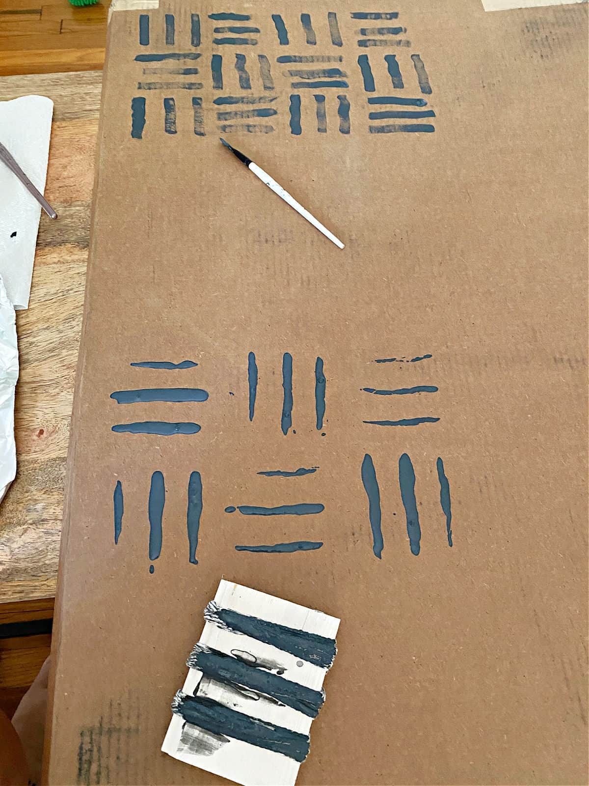 practicing DIY wall treatment on cardboard