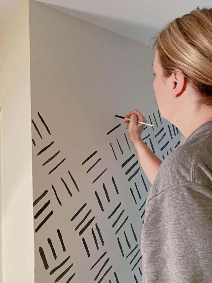 woman painting black lines on wall