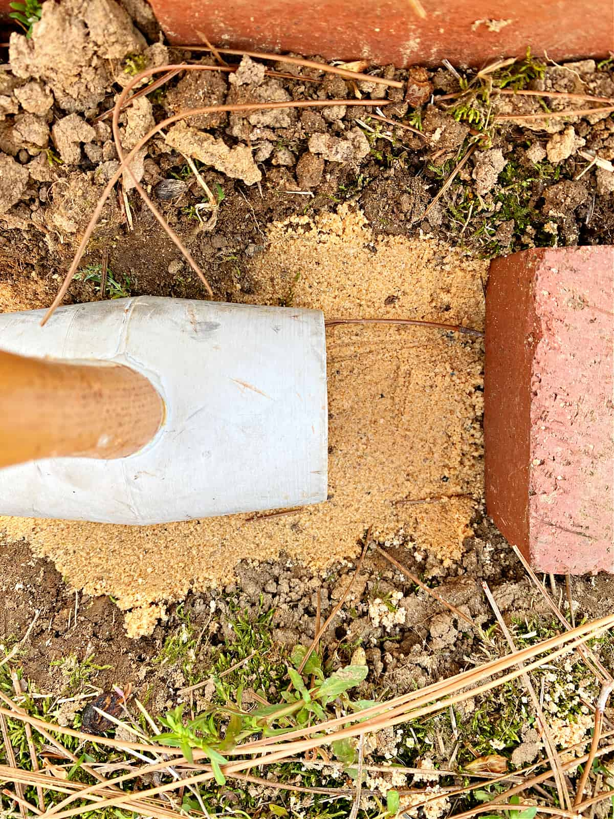 using a rubber mallet to tamp down sand