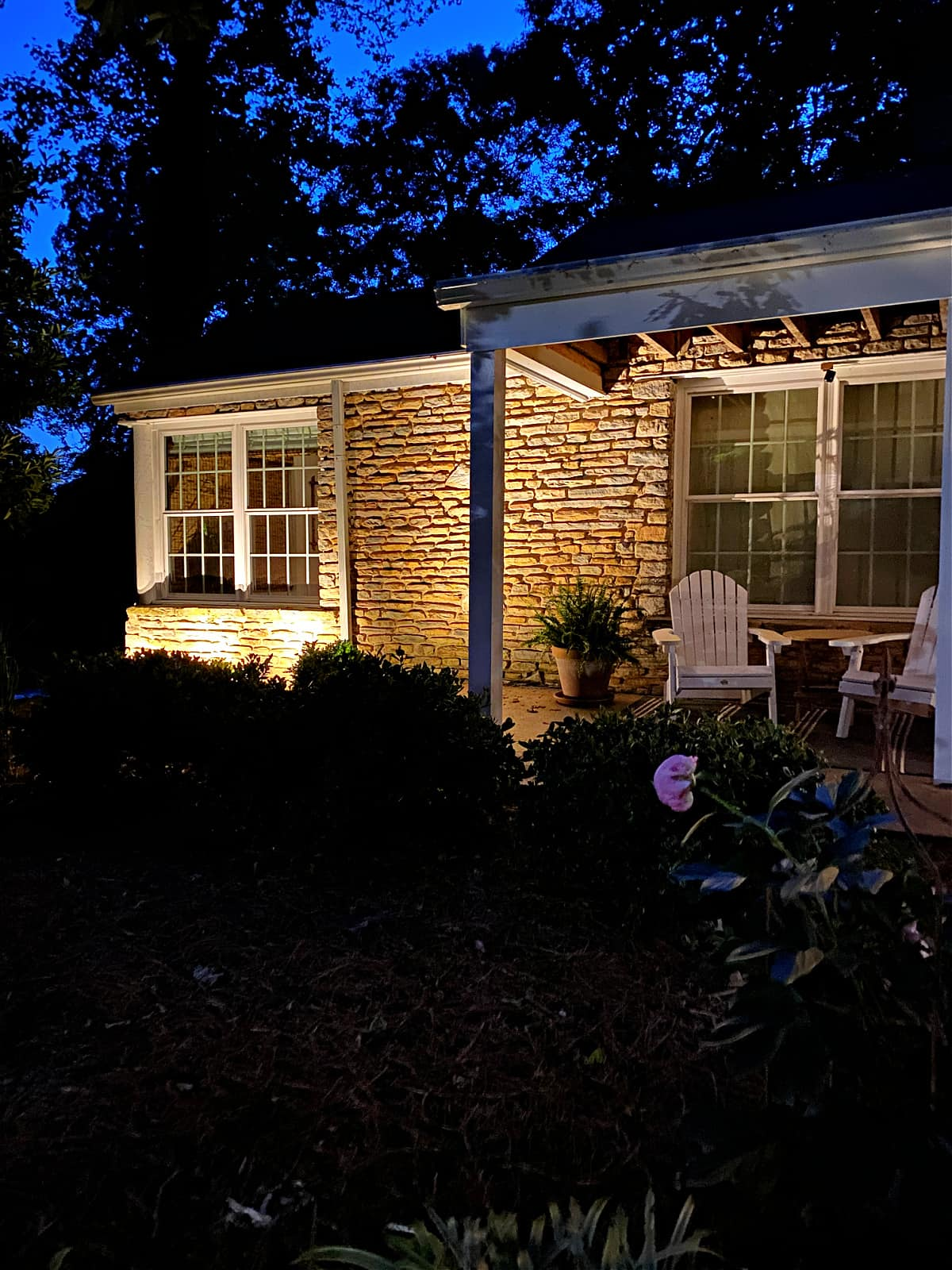 front of stone cottage with outdoor spot lights