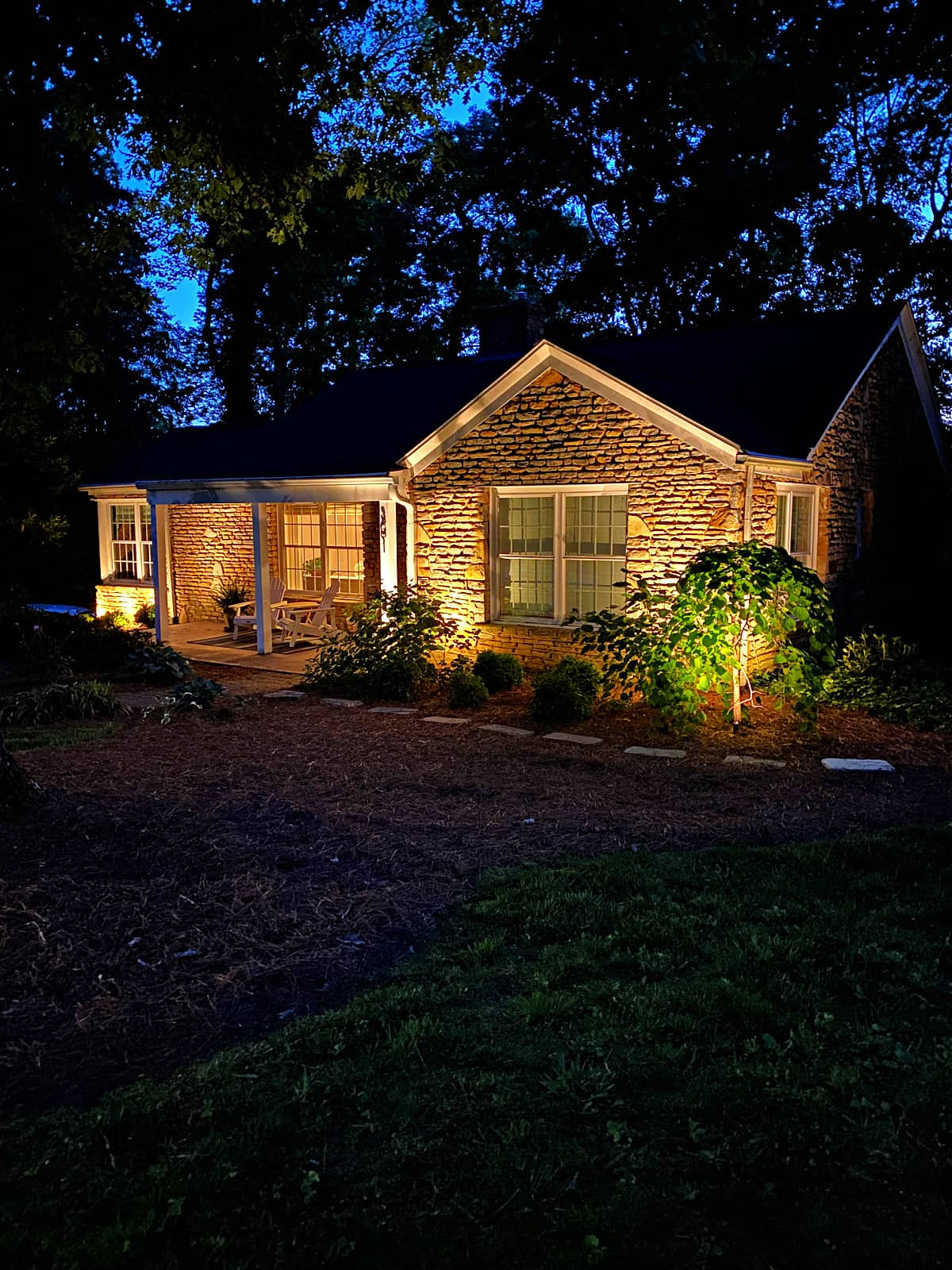 stone cottage at night with outdoor lights