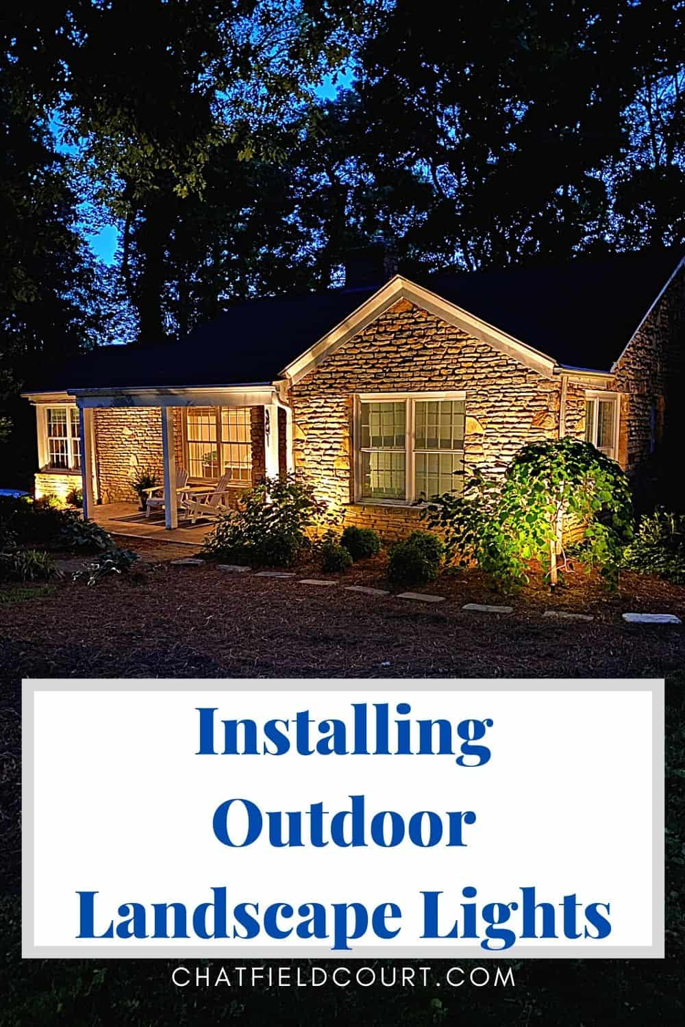 stone cottage at night with outdoor lights and large pinterest graphic
