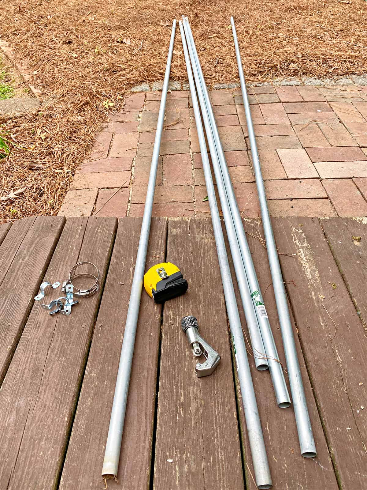 conduit pipe, tape measure, pipe cutter on ground
