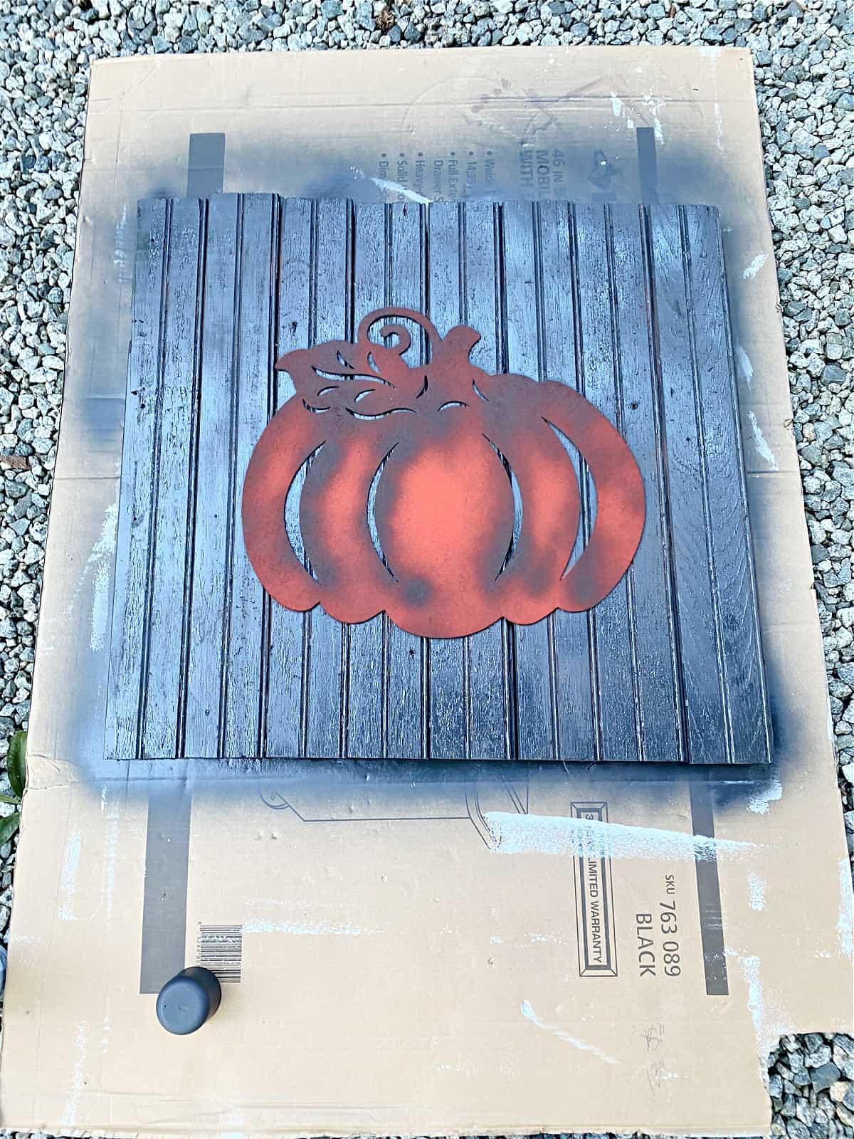 black painted pumpkin sign