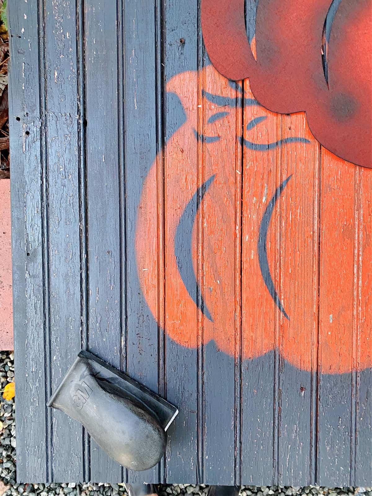 sanding block on pumpkin wood sign