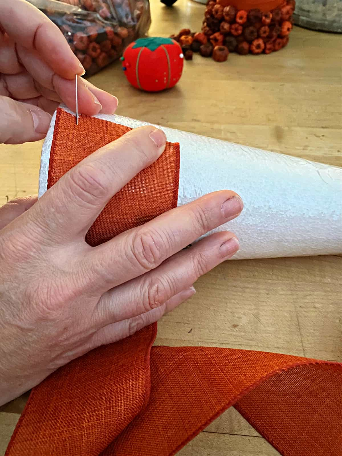 wrapping orange ribbon on styrofoam